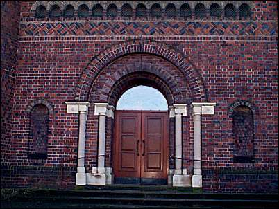 Central wide arched entrance in western gable